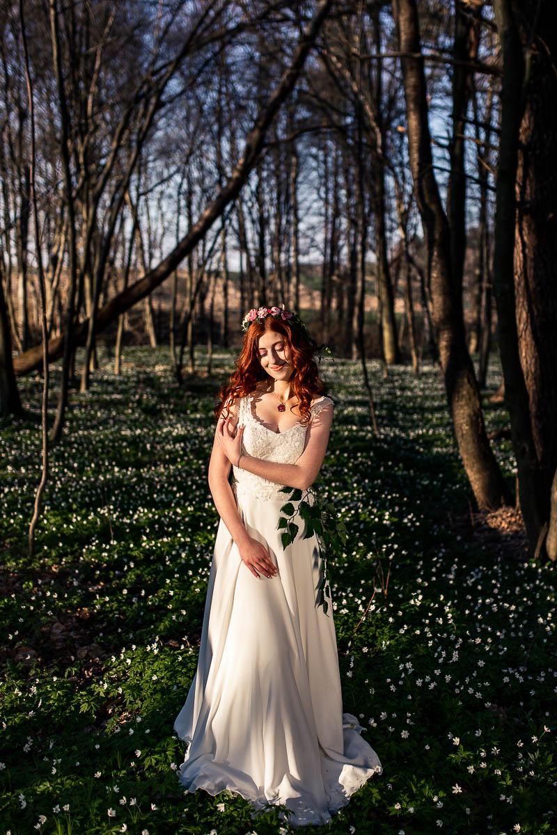 Pani wiosna otoczona kwitnącymi zawilcami stoi na sesja wiosenna na kolorowanka.