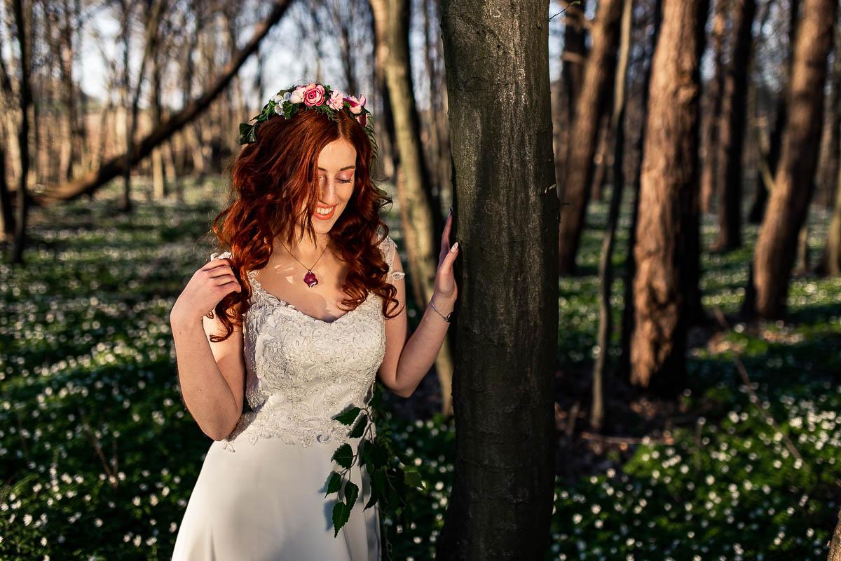 Pani Wiosna spogląda w dół i widać makijaż ślubny i wianek ślubny.