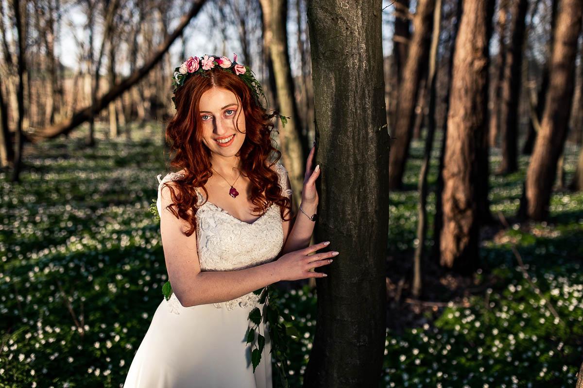 Pani Wiosna spogląda w obiektyw a dokoła niej widać zawilce na sesja kobieca.