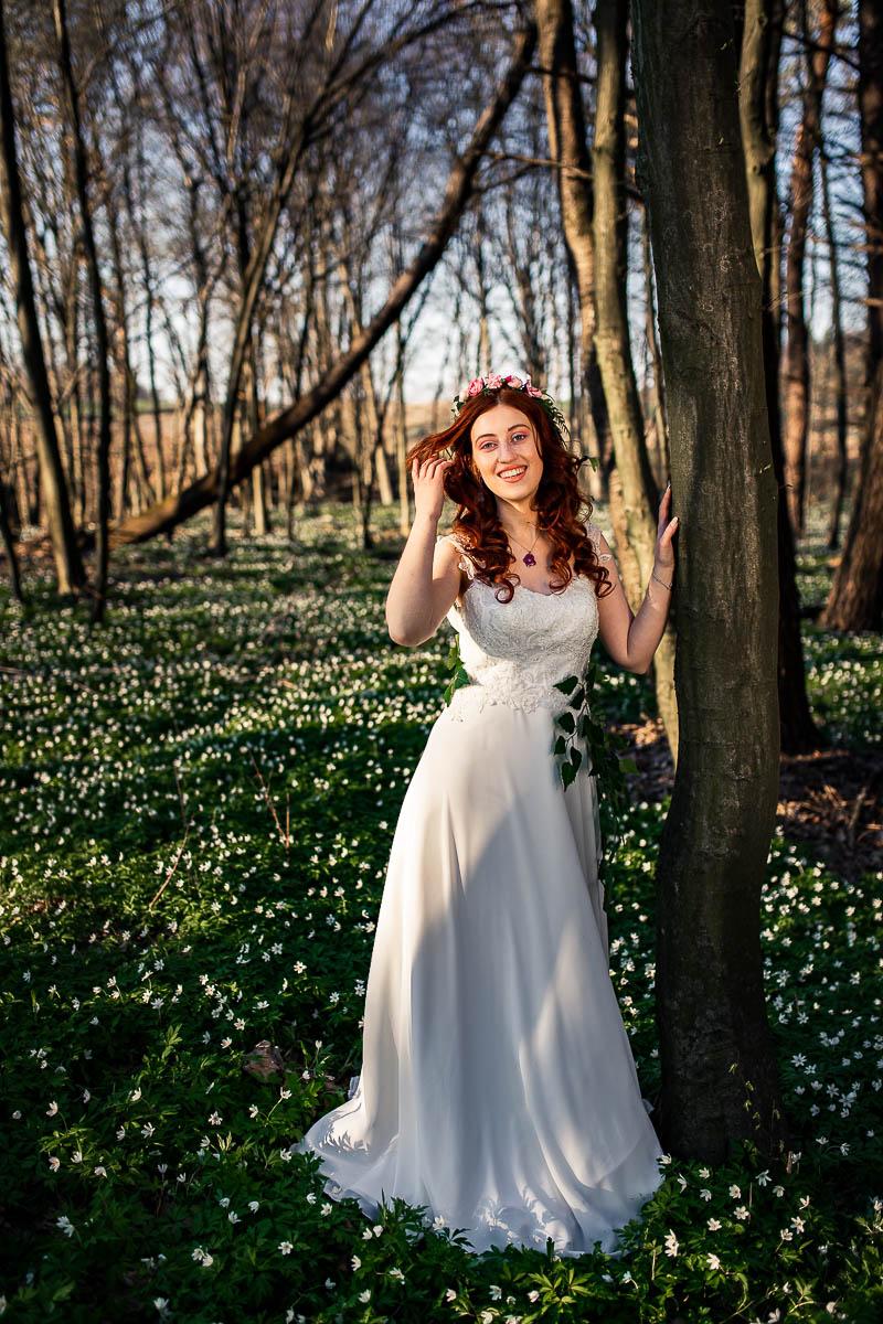 Oparta o drzewo odgarnie na bok włosy i szeroko się uśmiecha na sesja wiosenna.