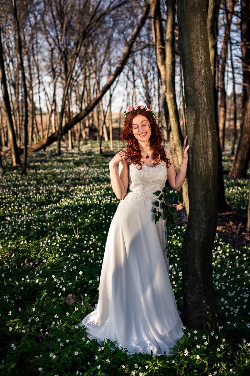 Spogląda na otaczające ją zawilce i wygląda jak na sesja ślubna w lesie.