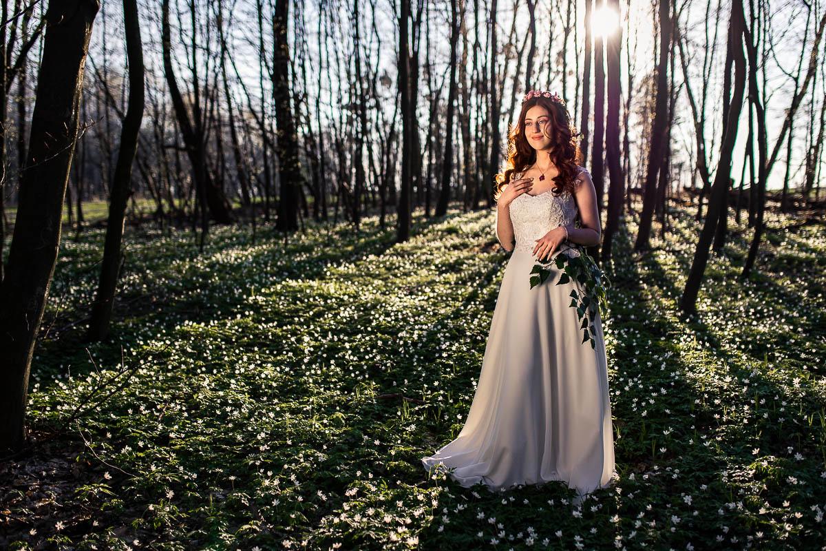 Promienie zachodzącego słońca oświetlają ją od tyłu i wygląda jak na sesja ślubna na Roztoczu.