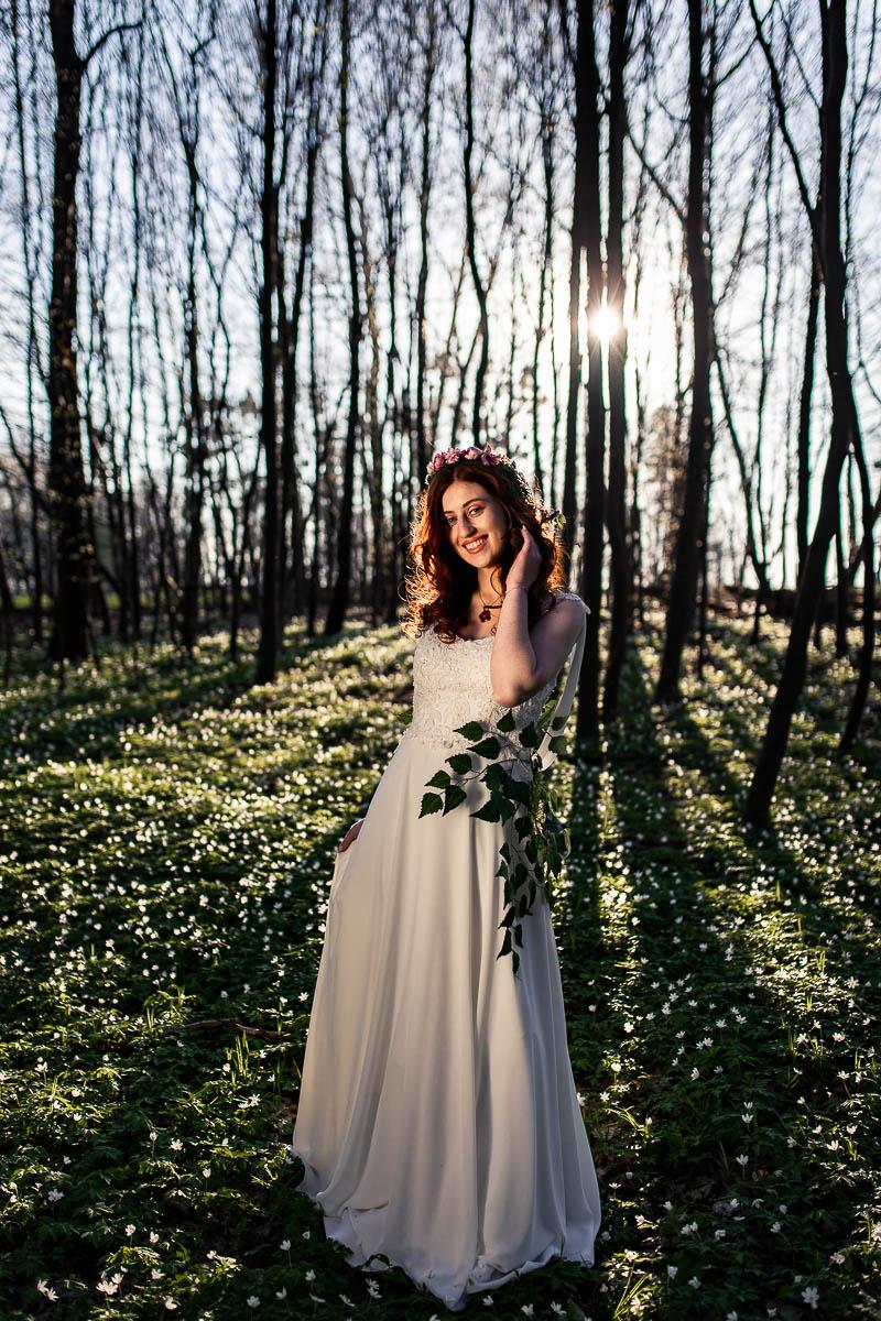 Uśmiechnięta stoi pośrodku lasu, a pod nogami ma zawilce jak na sesja wiosenna.