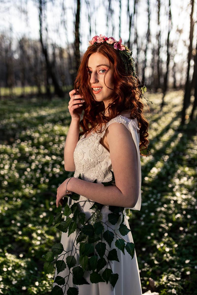 Pani Wiosna stoi i spogląda w stronę aparatu jak na sesja ślubna w plenerze.