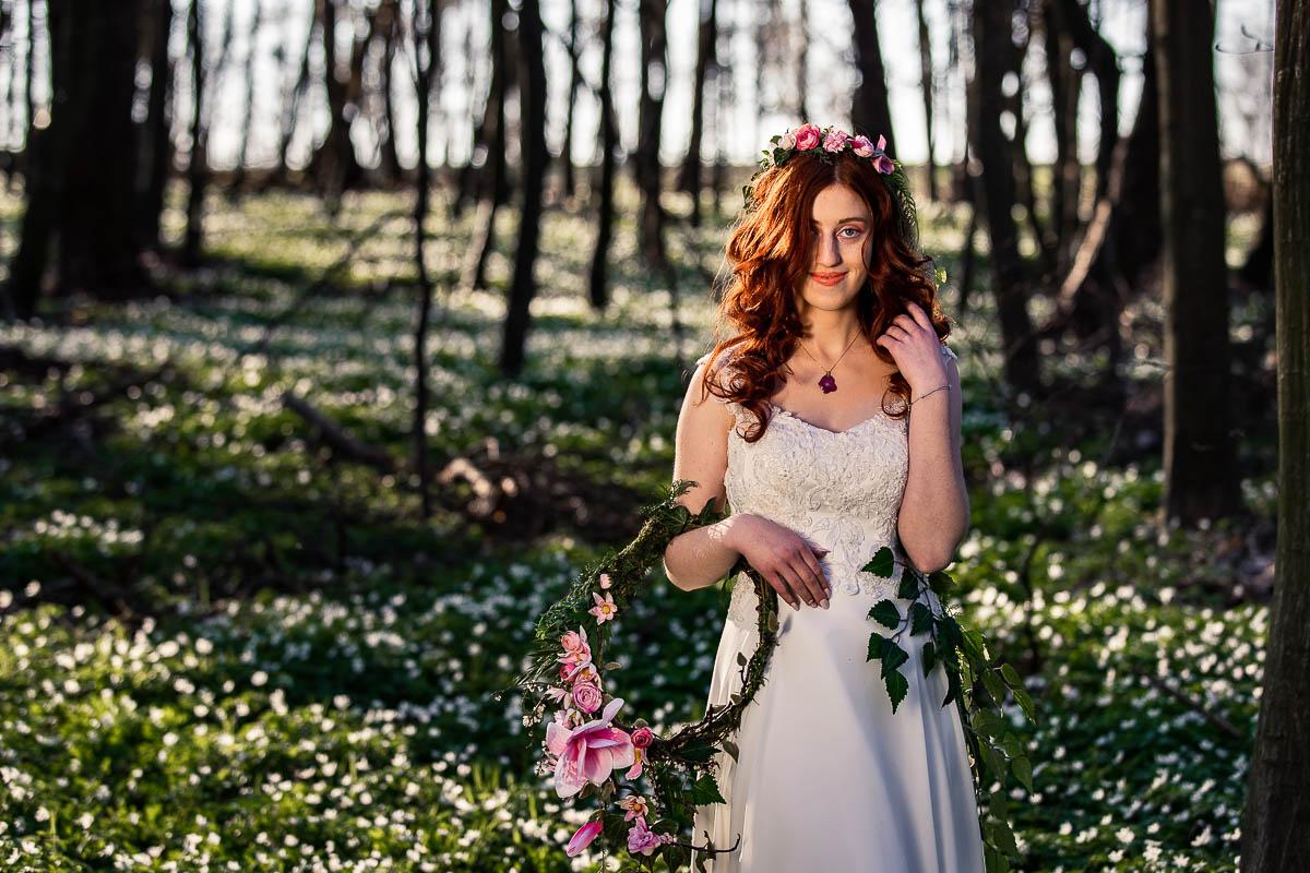 Dziewczyna trzyma ręku wianek i stoi pośrodku lasu.
