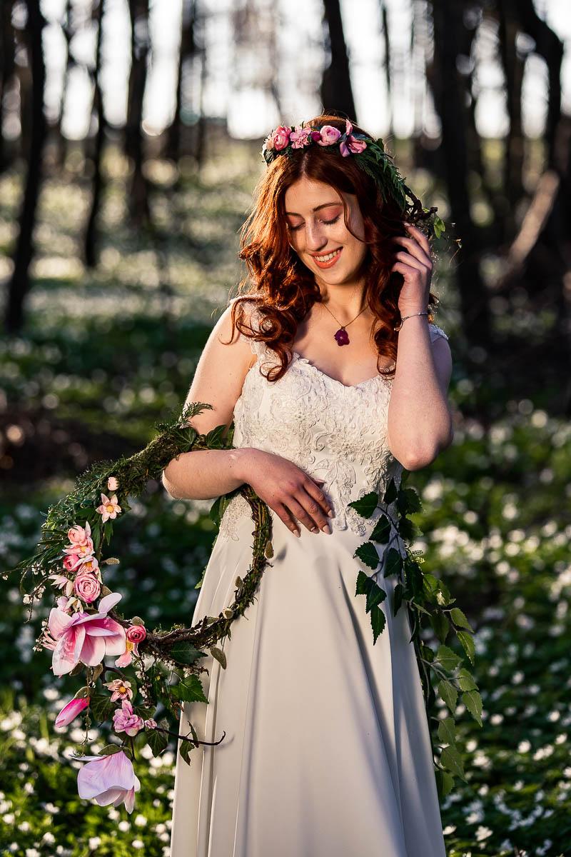 Pani Wiosna trzyma w ręku wianek i spogląda na niego jak na sesja zdjęciowa w lesie.