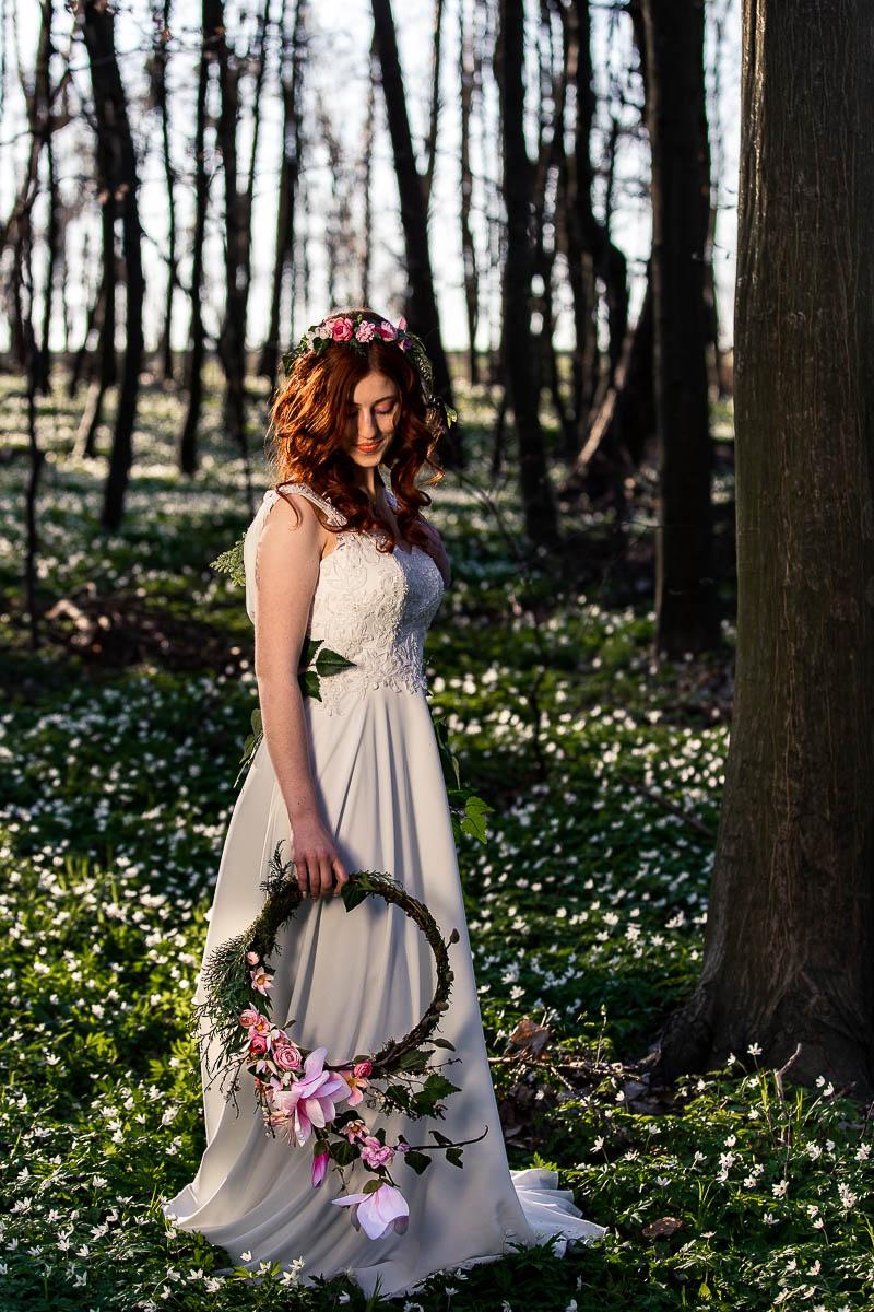 Pani Wiosna stoi pośród zawilców i patrzy na nie jak na sesja wiosenna.