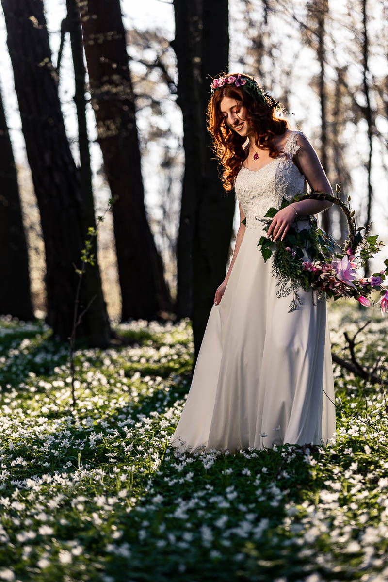 Patrzy na zawilce, a weku trzyma wianek ślubny na sesja ślubna.