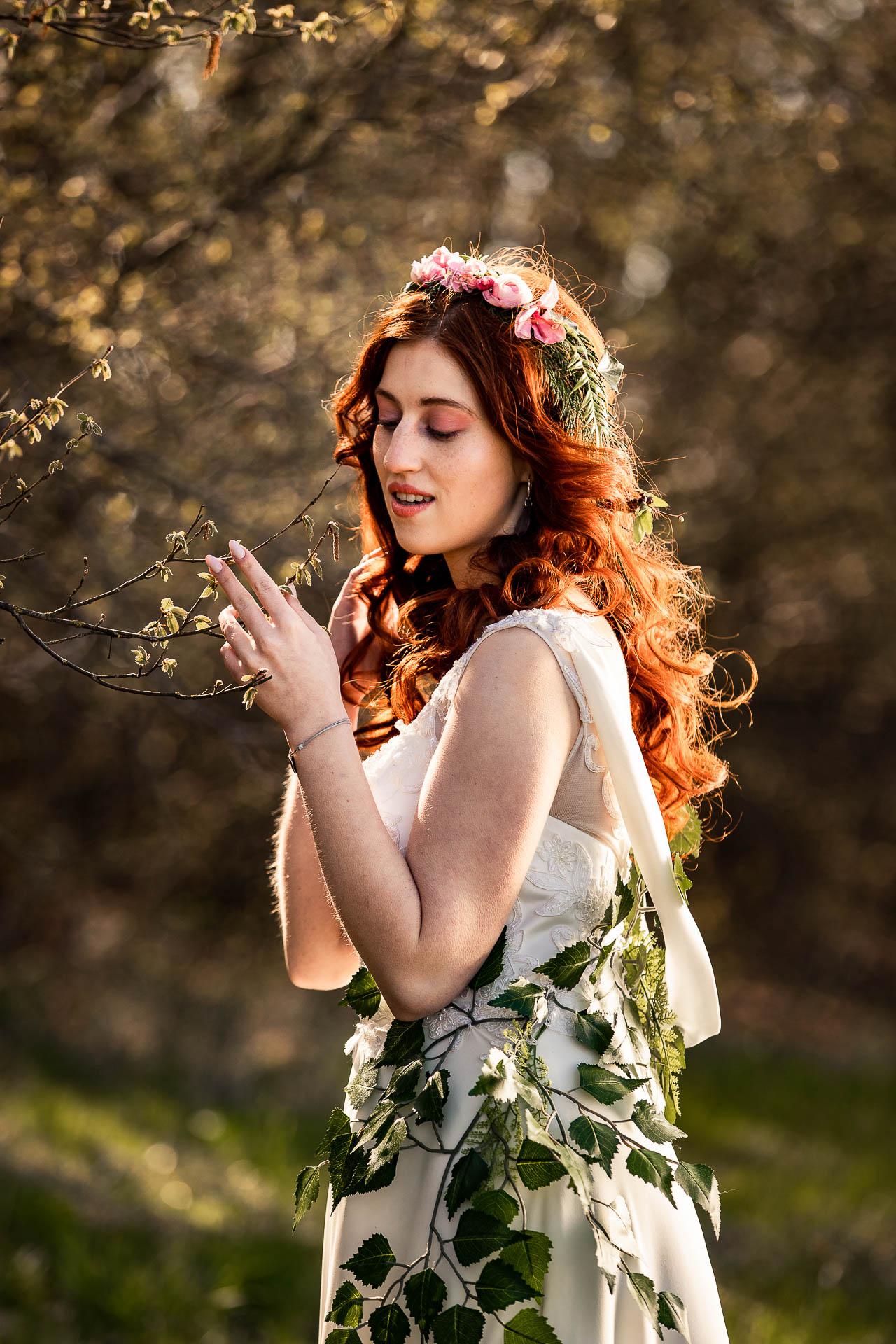 Delikatnie łapie w palce gałązkę jak na sesja wiosenna sensualna.