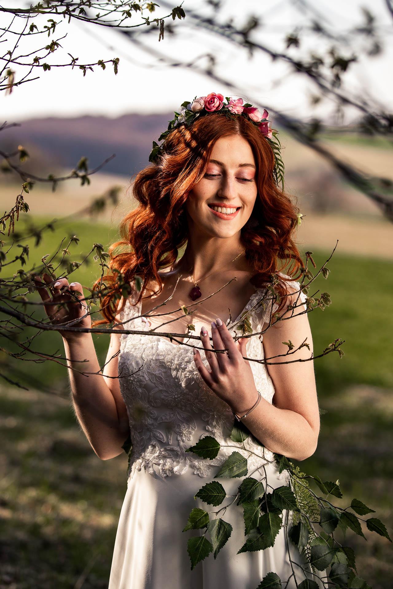 Słońce pięknie oświetla jej fryzura ślubna i wianek ślubny na głowie.