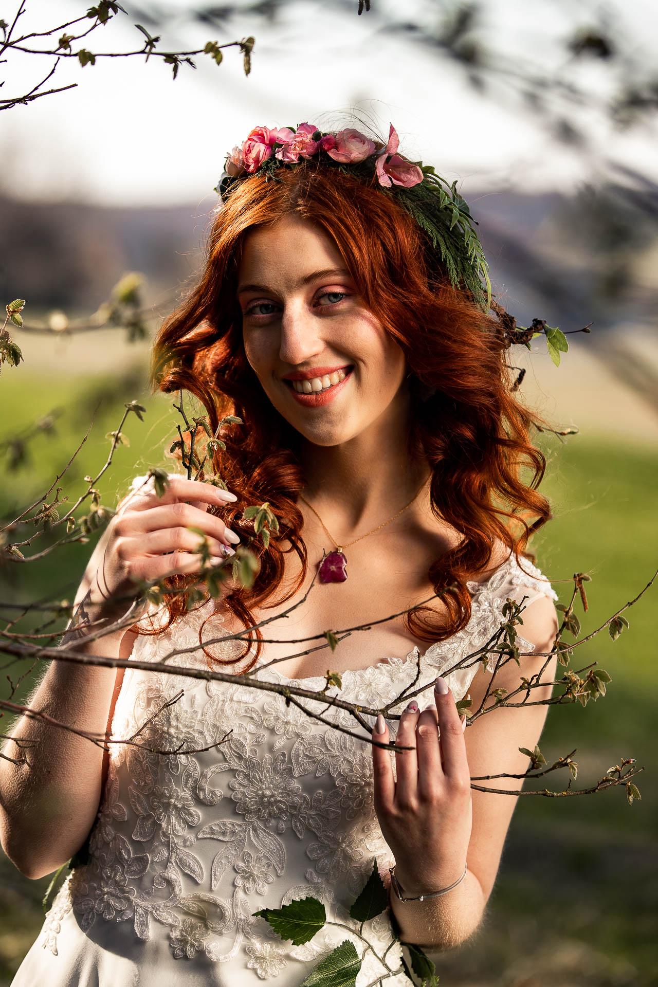 W rękach trzyma gałązkę i uśmiecha się na sesja wiosenna w plenerze.