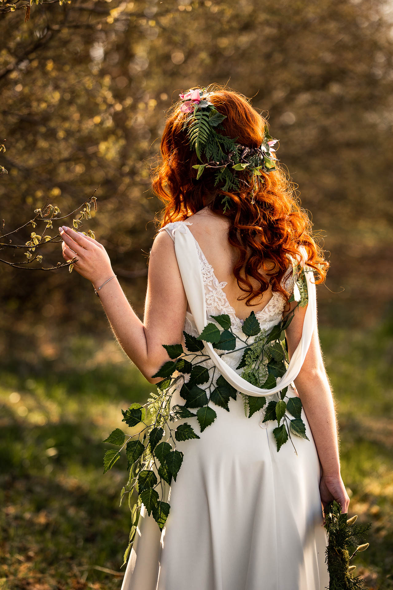 Patrzy na rozwijające się drzewa i dotyka je ręką jak na sesja sensualna.