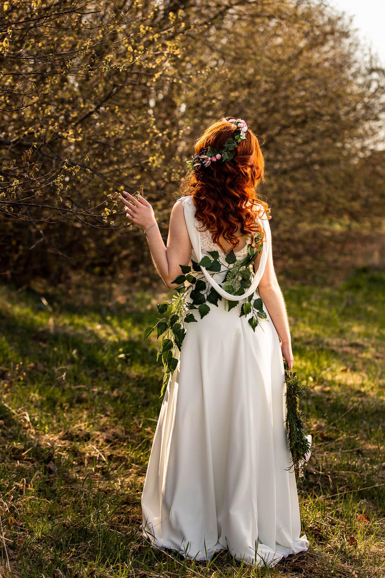 Stoi odwrócona tyłem. Widać fryzura ślubna i wianek ślubny na głowie.