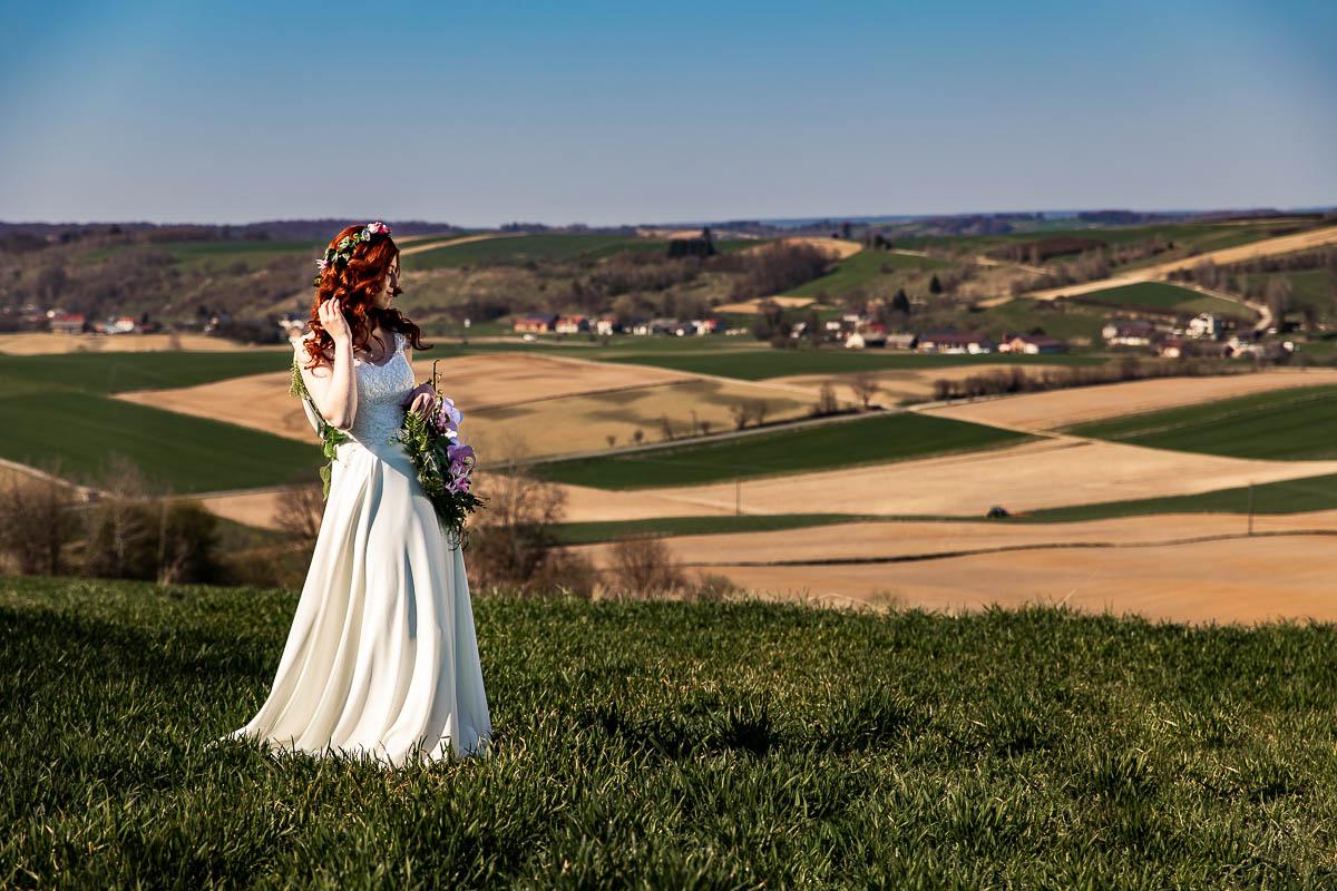 Stoi na wzniesieniu z widokiem na łąki i pola na sesja ślubna na Roztoczu.