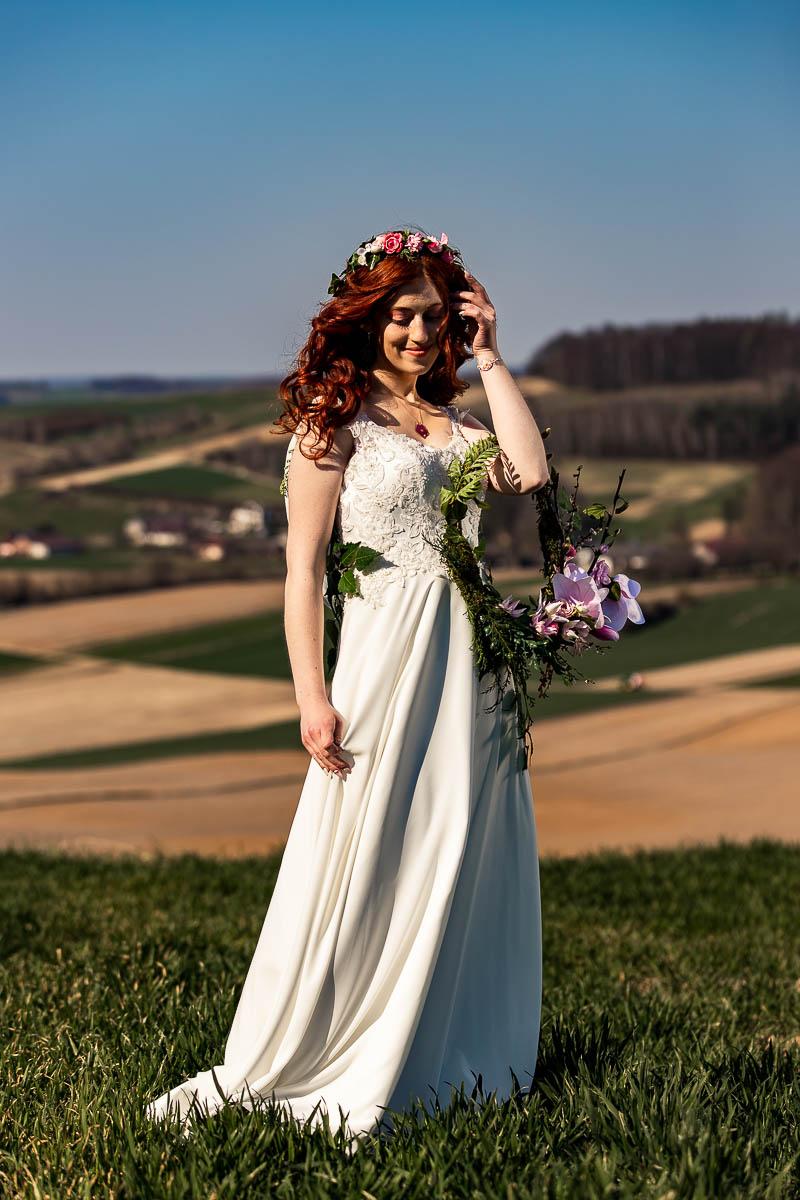 Zaczesuje włosy na sesja ślubna pośród łąk i pól. Za nią w oddali widać domy.