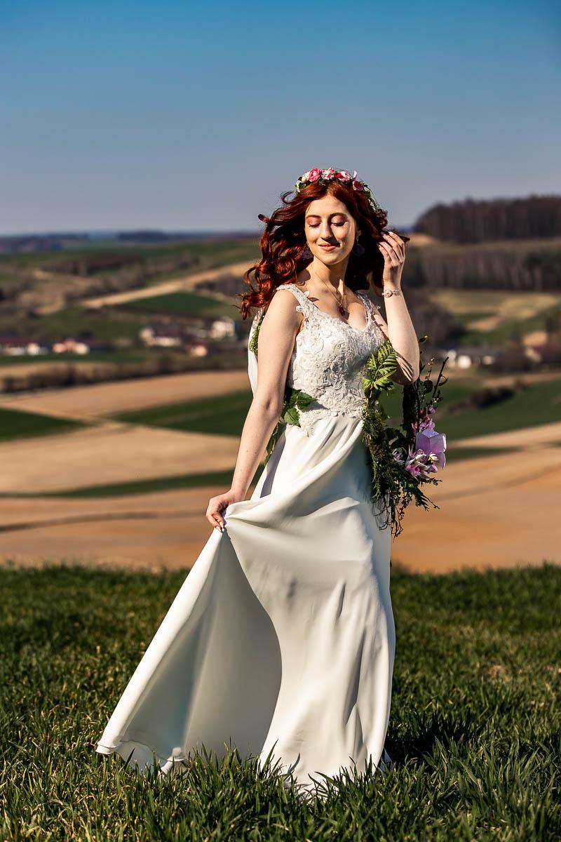 Słońce oświetla jej twarz a na jej ręku wisi wianek ślubny jak na sesja ślubna.