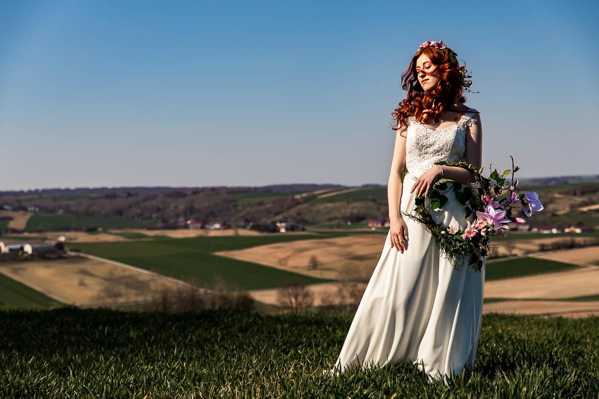 Patrzy w bok, a za nią widać łąki i pola. Stoi na sesja wiosenna kobieca.