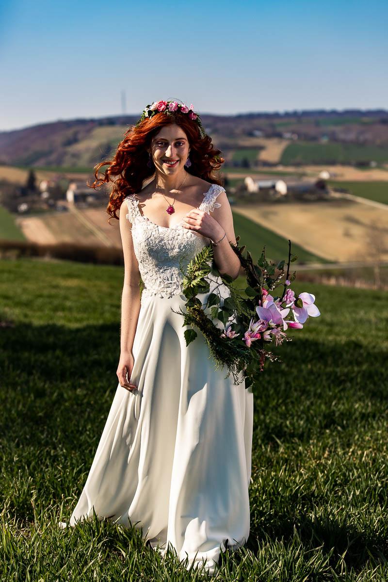 Słońce oświetla jej włosy i ślubny wianek. Wygląda na sesja wiosenna w plenerze.