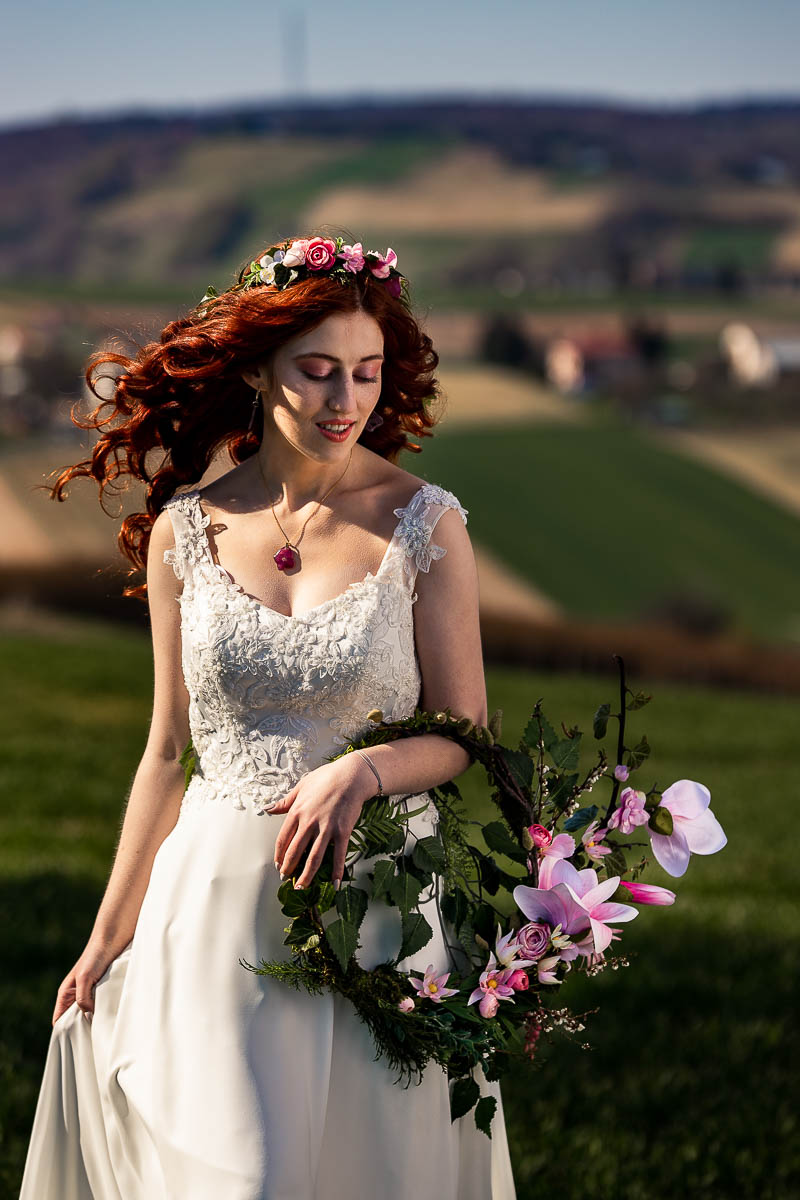 Idzie wśród pól w ręku trzymając ślubny wianek jak na sesja ślubna w plenerze.