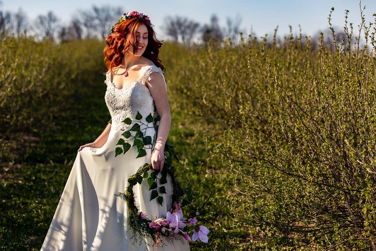 Tańczy wśród krzewów w ręce trzymając ślubny wianek.