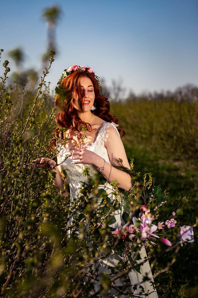 Wiatr rozwiewa jej włosy zasłaniając twarz jak na sesja sensualna.