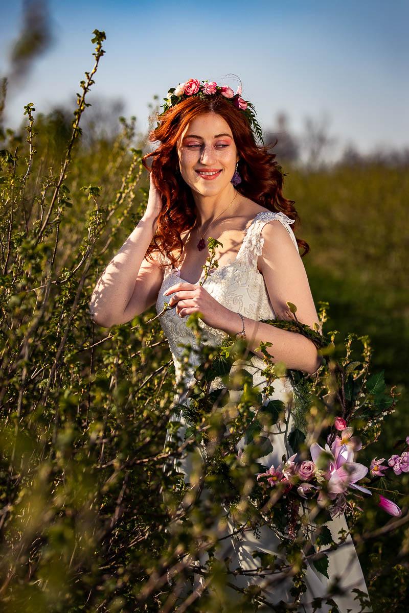 Stoi wśród rozwijających się krzewów i spogląda w bok jak na sesja zdjęciowa kobieca.