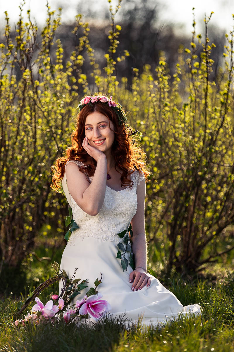 Klęczy na trawie, a słońce oświetla jaj fryzura ślubna wiosenna.