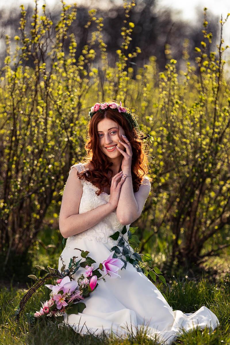 Uśmiechnięta dotyka ręką twarzy jak na wiosenna sesja kobieca.