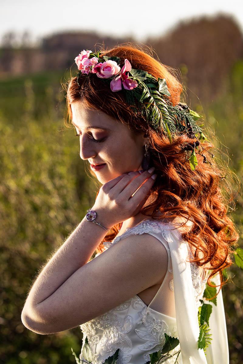 Słońce oświetla jej twarz, a na głowie widać wianek ślubny.