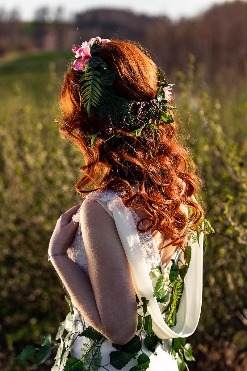 Stoi odwrócona tyłem. Widać uczesane włosy ja fryzura ślubna.
