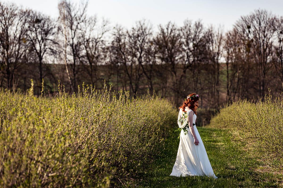 Pole z rosnącymi krzewami i stojąca między nimi jak na sesja wiosenna kobieca Pani Wiosna.