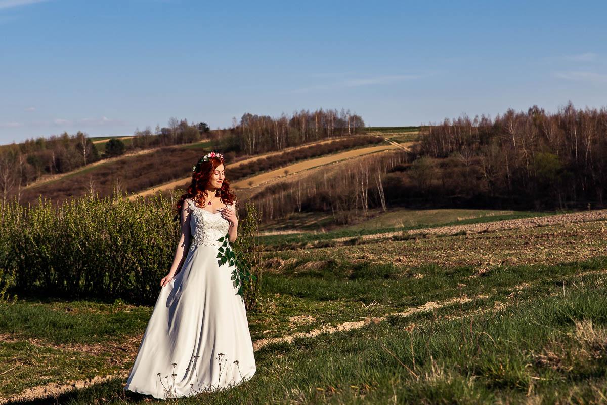Dziewczyna idzie przez pola w promieniach zachodzącego słońca.