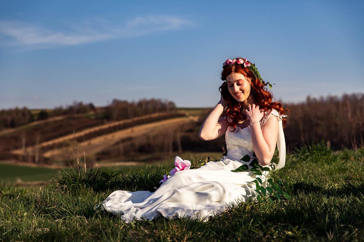 Siedzi na trawie i odgarnia włosy jak na sesja kobieca w plenerze.