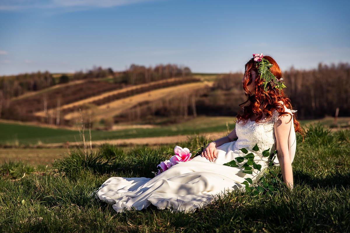 Siedzi na trawie wpatrzona w dal jak na wiosenna sesja ślubna w plenerze.