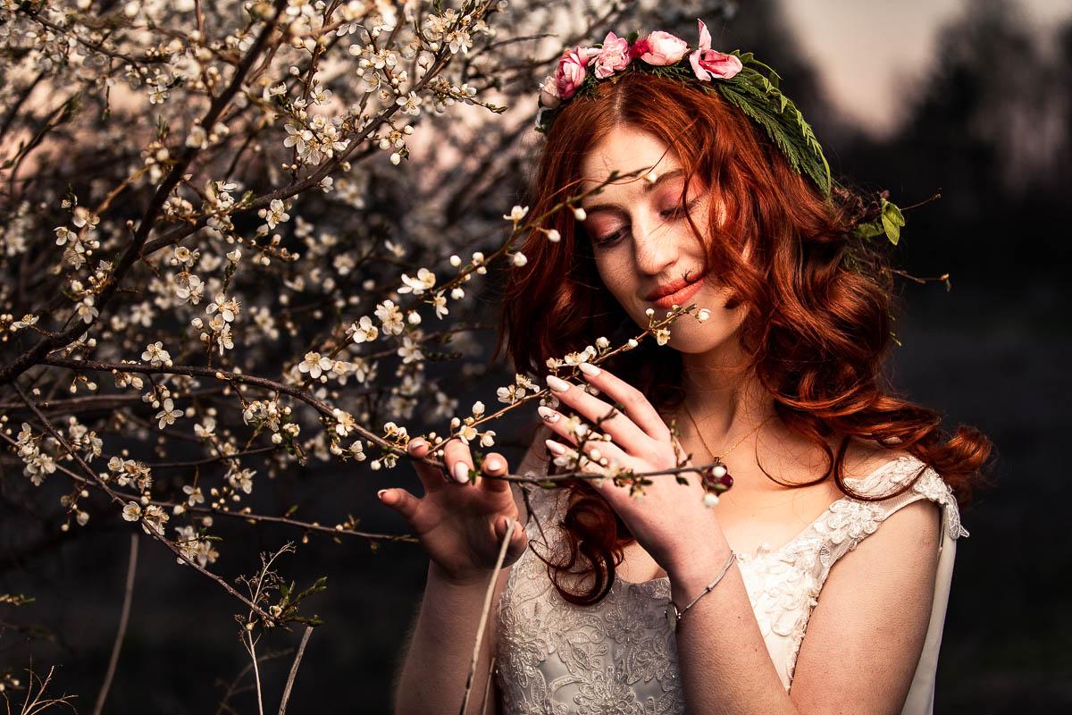 Zachód słońca. Pani Wiosna trzyma w rękach kwitnące gałązki jabłoni.