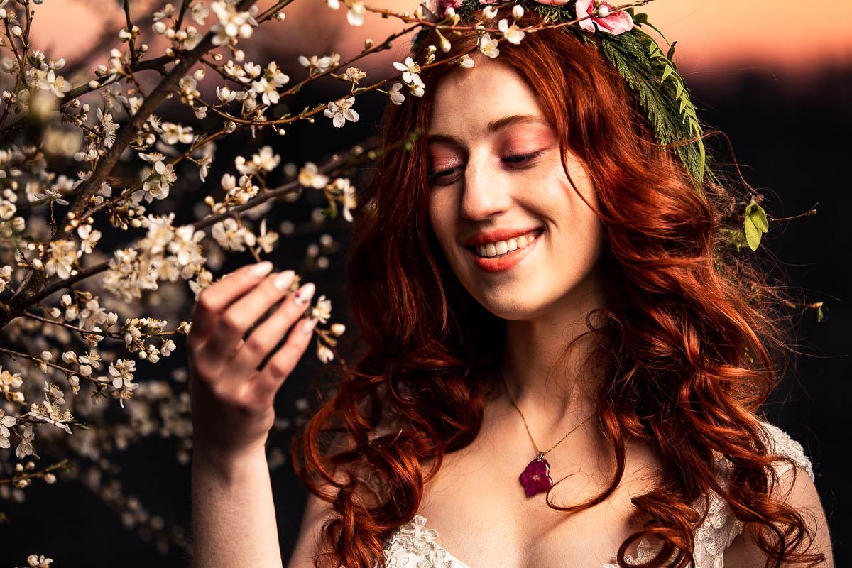 Uśmiechnięta patrzy na kwitnące gałązki jabłoni jak na sesji wiosenna kobieca.
