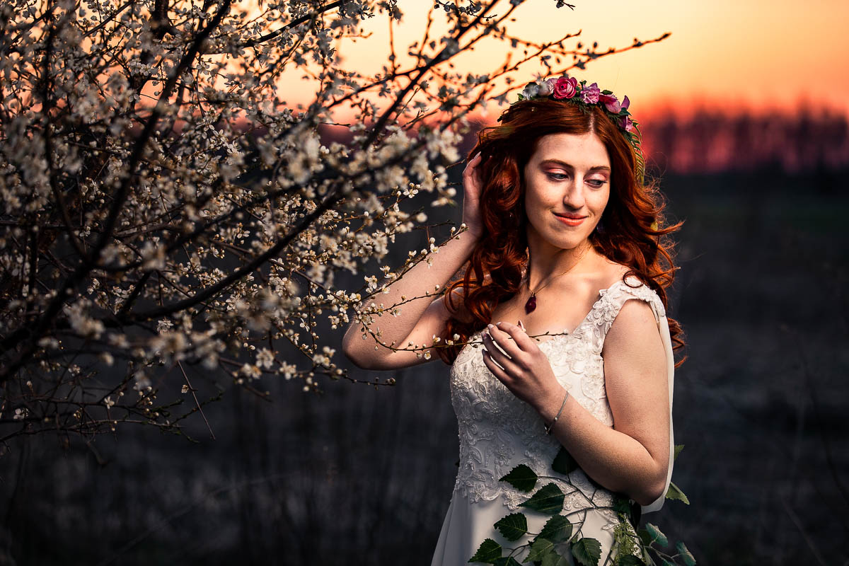 Pani Wiosna odgarnia włosy przy zachodzie słońca jak na sesja sensualna.