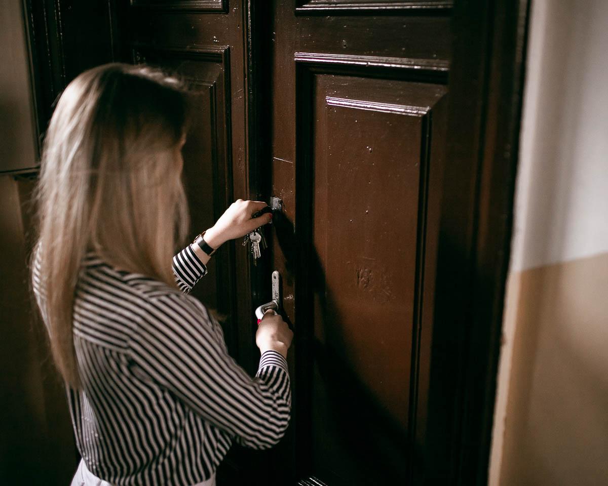 Klucz w drzwiach. Dziewczyna otwiera zamek.