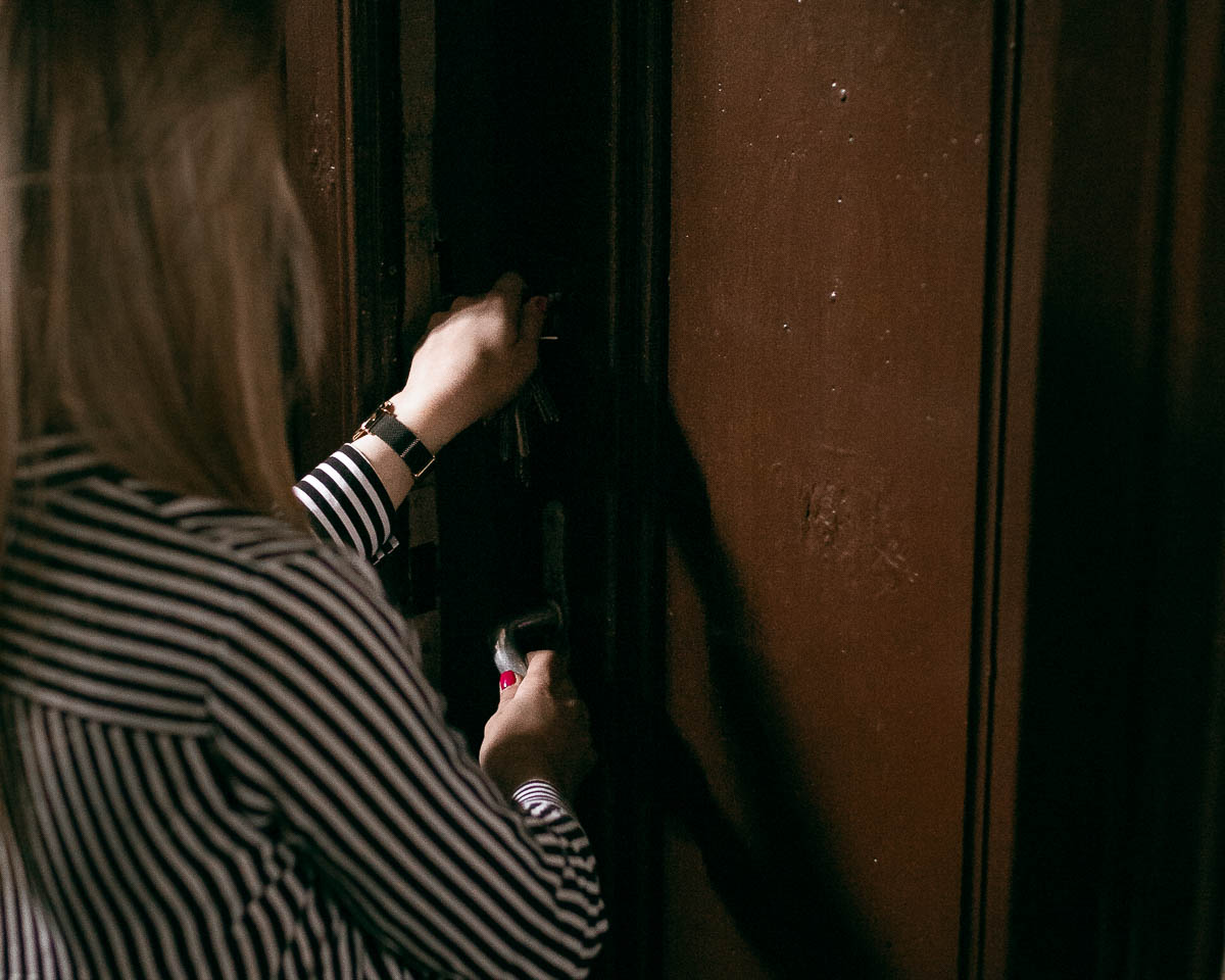 Zbliżenie na drzwi i klucz w drzwiach. Dziewczyna odwrócona tyłem do fotograf Zamość.