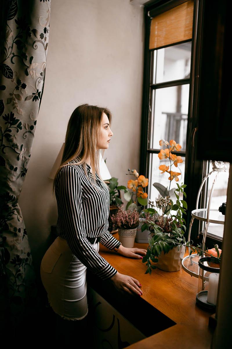 Okno, szeroki parapet, a na nim kwiaty: storczyki, wrzosy i inne jak na sesja w lesie.