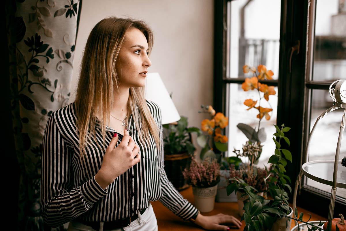Dziewczyna stoi przy oknie i patrzy w dal na sesje zdjęciowe rodzinne.