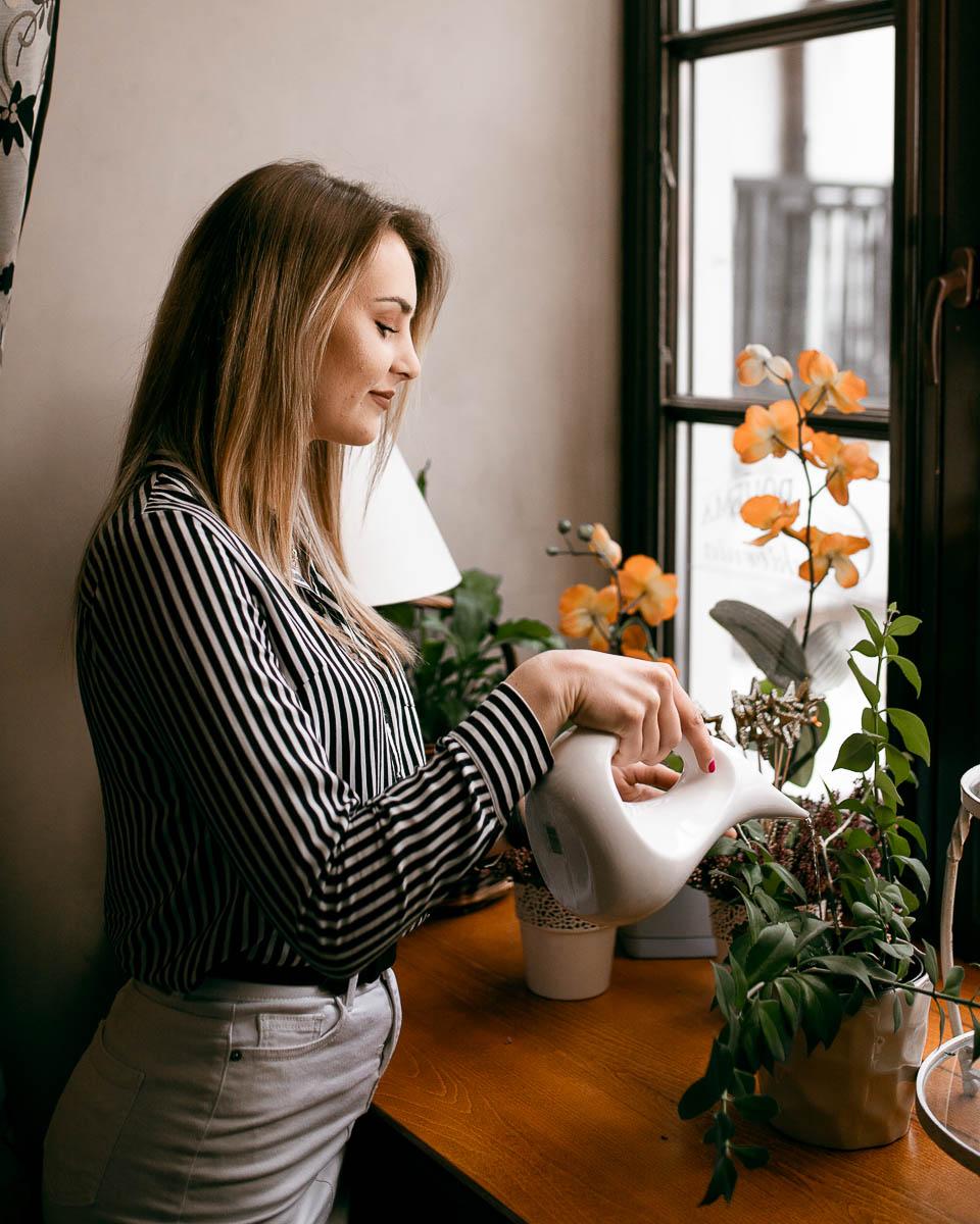 Podlewa kwiaty białą porcelanową podlewaczką jak na profesjonalna sesja zdjęciowa.