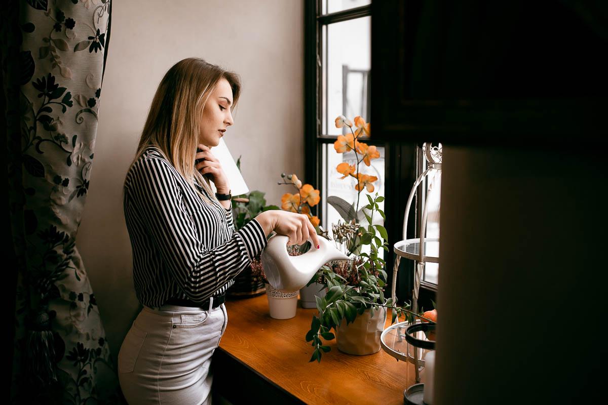 Zza ściany widać jak dziewczyna podlewa kwiaty przytrzymując sobie włosy na sesja sensualna.