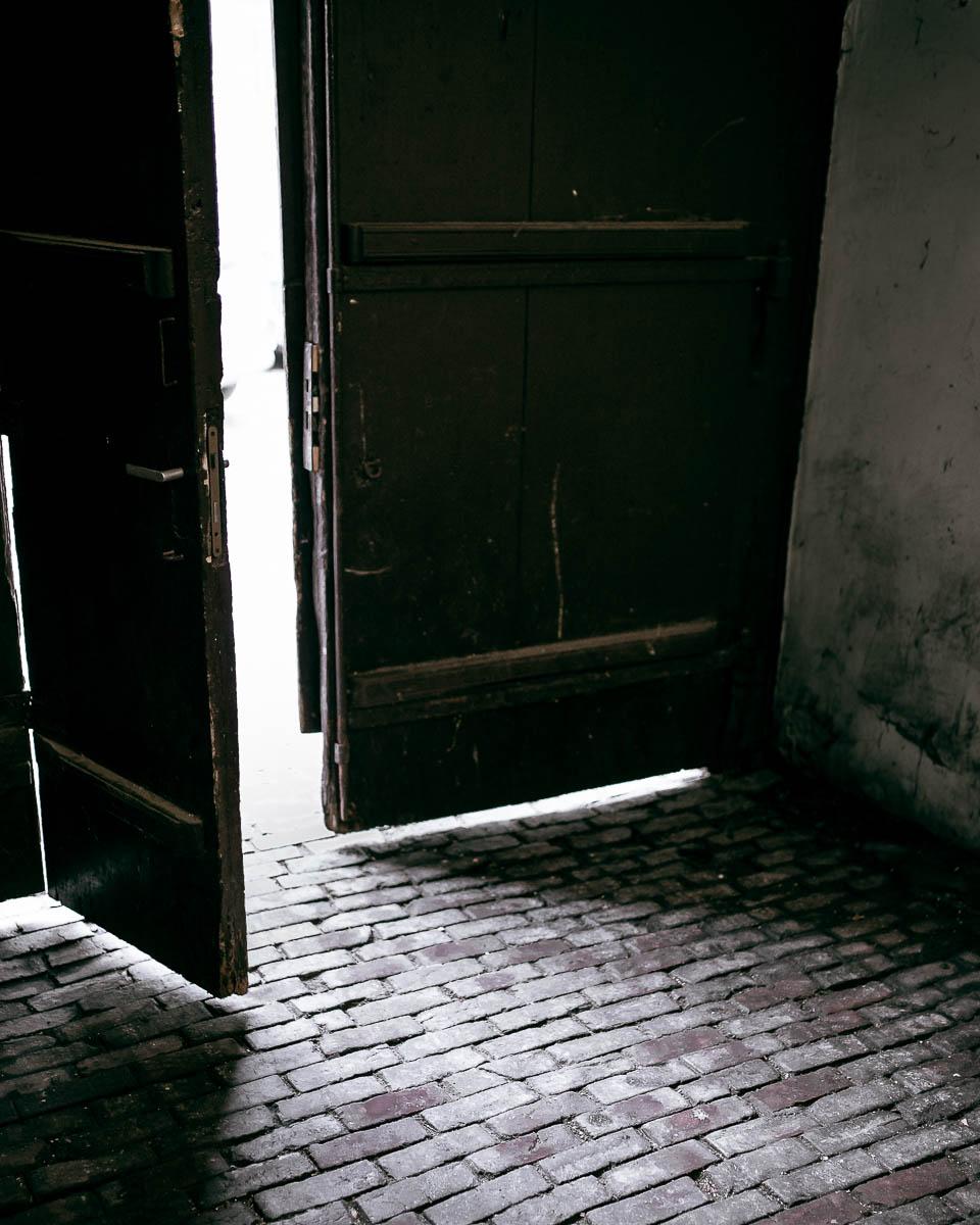 Brama wejściowa do kamienicy. Brukowany wjazd na stare miasto w Zamościu.