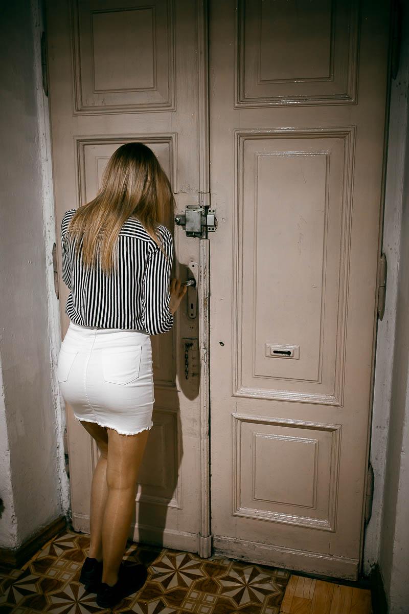 Drzwi wejściowe i dziewczyna patrząca przez wizjer na klatkę schodową na stara miasto w Zamościu.