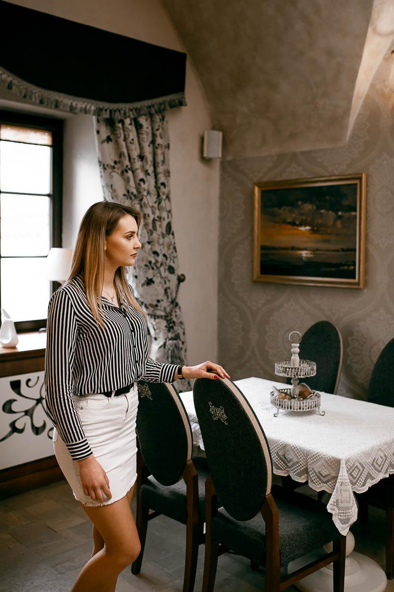 Ładne mieszkanie. Stół z krzesłami, na nim obrus a na ścianach obraz z zachodem słońca na sesja w plenerze.