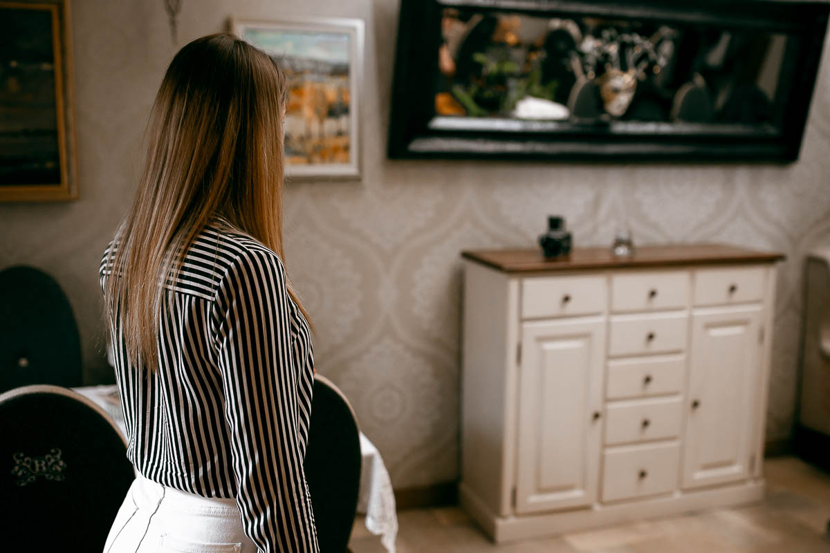 Dziewczyna spogląda w stronę komody od fotograf ślubny Zamość, na której stoi szklany wąski wazon na kwiaty.