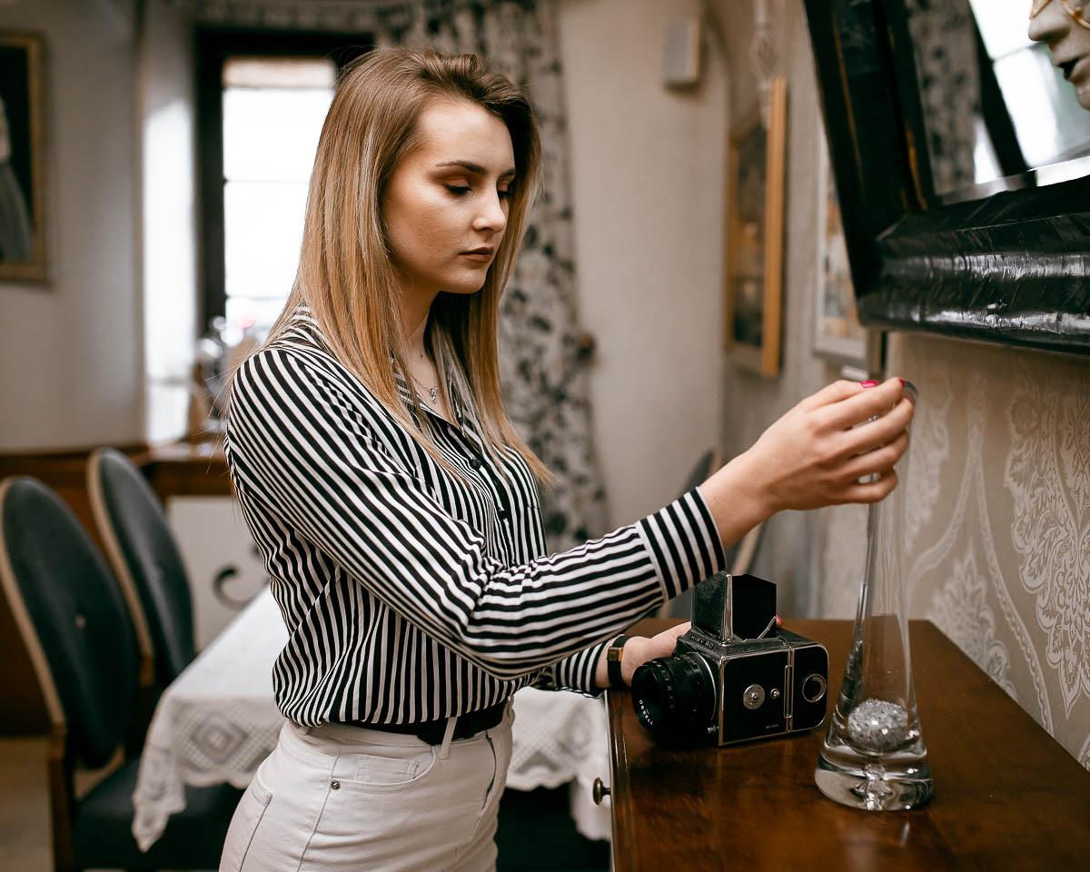 Dziewczyna dotyka szklanego wazonu jak na sesja zdjęciowa na prezent.
