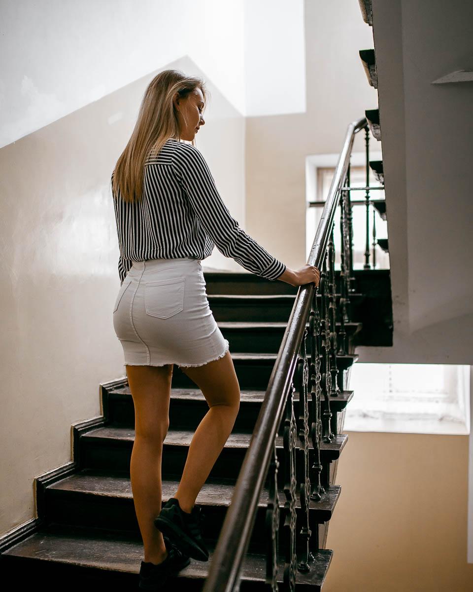 Dziewczyna w białej spódnicy i bluzce w czarne paski odwrócona tyłem wchodzi po schodach na sesja zdjęciowa.