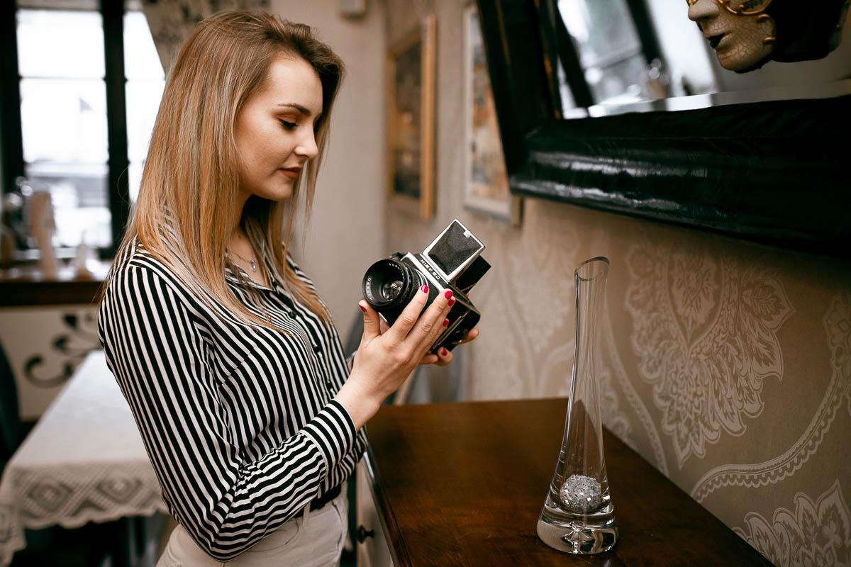 Z zaciekawieniem ogląda aparat Kiev 80 jak na sesja fotograficzna Lublin.